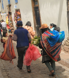 The woman carry their babies around in blankets as they conduct their business during the day.